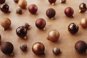 Christmas golden glitter baubles and balls on rustic background. Modern gold and brown shiny tree decorations. Seasons greetings. Merry Christmas. Happy holidays