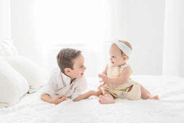 A Brother And Sister Sitting Together On A Bed