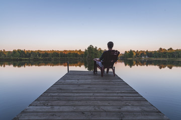 Young man relaxing on an Adirondack chair and looking at a calm river at sunset. Muskoka, Ontario, Canada.