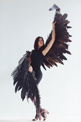 Fallen black angel with wings. Sexual woman.