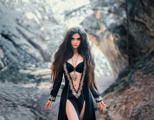 enchanted girl in a black dress with open tummy, bare legs and silver embroidery, with lush dark long hair and magical amulet around her neck. clairvoyant prepares a curse with a misty frozen forest