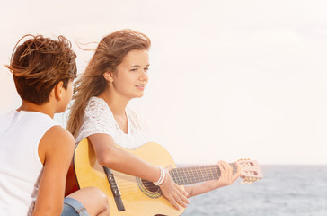 Young boy listening to girl playing guitar outdoor