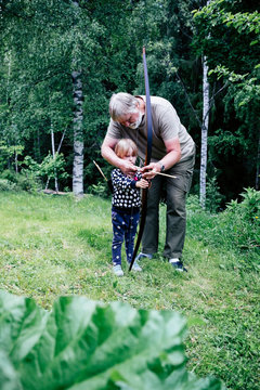 Grandfather guiding granddaughter in aiming arrow while standing on grassy field at forest