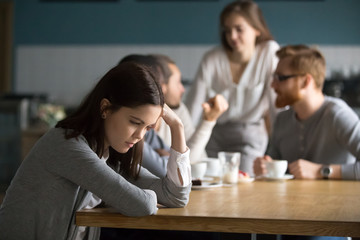 Upset young girl sit alone at coffee table in cafe feeling lonely or offended, sad female loner avoid talking to people, student outsider suffer from discrimination, lacking friends or company