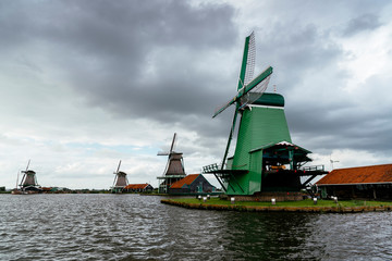 View of traditional windmills by canal against cloudy sky during sunset
