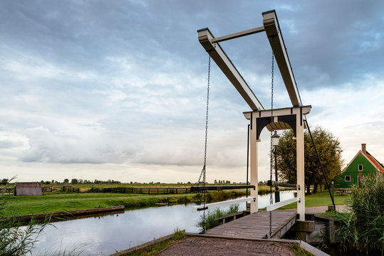 footbridge over canal by landscape against cloudy sky during sunset