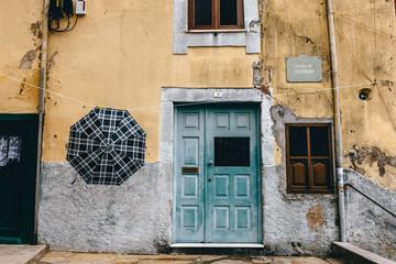 Ein Regenschirm hängt vor einem Haus in einer kleinen Gasse in Porto