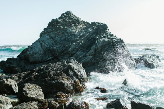 Waves splashing on rocks at beach against sky during sunny day