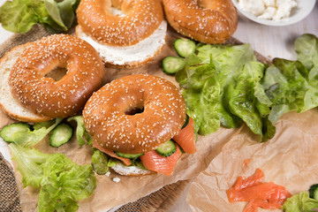 Fresh homemade bagel sandwiches with smoked salmon and low fat cream cheese. Healthy breakfast food on rustic wooden background