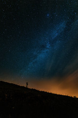 Low angle view of silhouette hill against star field at night