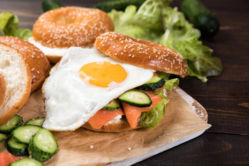 Fresh homemade bagel sandwiches with smoked salmon and low fat cream cheese and an egg. Healthy breakfast food on rustic wooden background