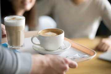 Close up of waiter holding aromatic cappuccino and latte on tray bringing order to cafe guests, coffeeshop worker give hot drinks to visitors, cups with delicious fresh brewed coffee on platter