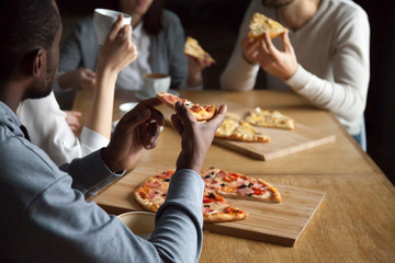 Close up of diverse friends hang out in pizzeria enjoy pizza and coffee, multiethnic young people talk having fun in Italian restaurant eating tasty food, millennial colleagues meet in cafe for lunch
