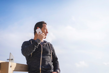 Low angle view of man listening to smart phone while standing at beach against sky during sunny day
