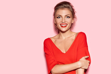 Wall Mural - Portrait of truly happy female looking at camera in studio. Well-dressed girl in red blouse with bright lipstick on pink background. Concept of youth and happiness