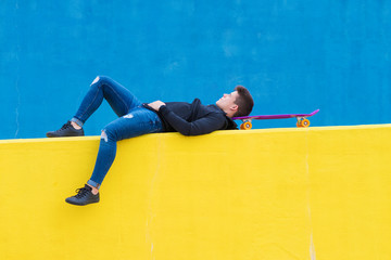 Man looking away while lying with skateboard on yellow retaining wall in city