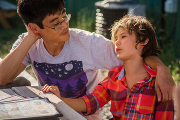 Father and son talking while sitting at wooden table in yard
