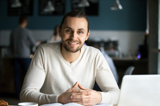 Portrait of smiling millennial man sitting in cafe with laptop and books on table, happy young guy work in coffeeshop using computer, male student look at camera busy preparing report in coffeehouse