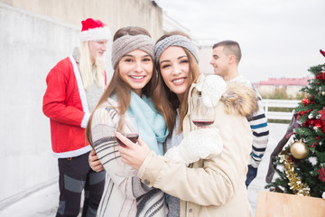 Young women with friends on balcony celebrating Christmas