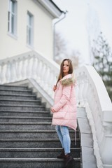 Beautiful young girl in white sweater and pink jacket walking in the Park.