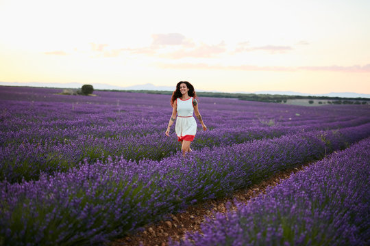 Young woman running between violet lavender field