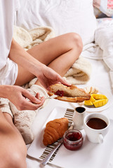top view of a woman in wool knitted socks sitting on the bed with breakfast and spreads croissant with jam. a plate with croissants, jam and fruit and cup of coffee for breakfast in bed.