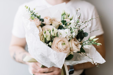 Very nice young man holding beautiful blossoming flower bouquet of fresh hanoi ranunculus, mattiola, eustoma, eucalyptus  in white colors on the grey background