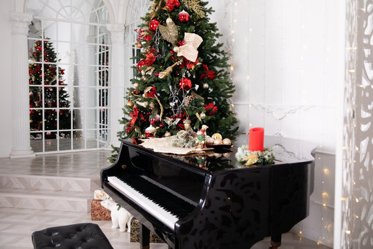 Christmas tree decorated with toys, lights and garland and piano