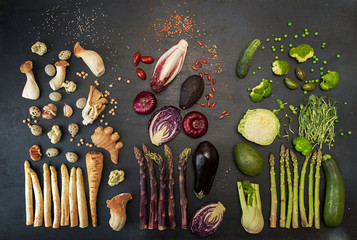 Flat lay of various fresh vegetables on black table