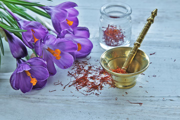 Crocus flowers with saffron spices and pestle  on wooden background