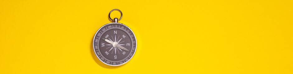 Black compass on yellow background, travel concept