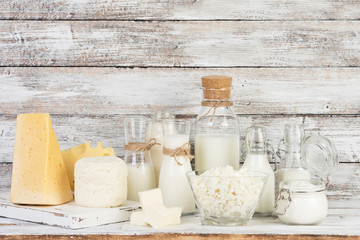 Fermented milk products: milk, kefir, sour cream, cottage cheese, butter, cheese on a white wooden table
