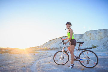 Young beautiful woman with a sport bike, soft focus background