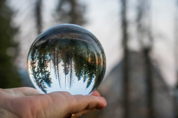 Sunset over Mountains with Forest and Moon Captured in Glass Ball Held in Palm Wall mural