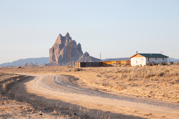 Fototapete - View of an old house in a dry desert with a Shiprock mountain peak in the background during a vibrant sunny sunrise.Taken at Rattlesnake, New Mexico, United States.