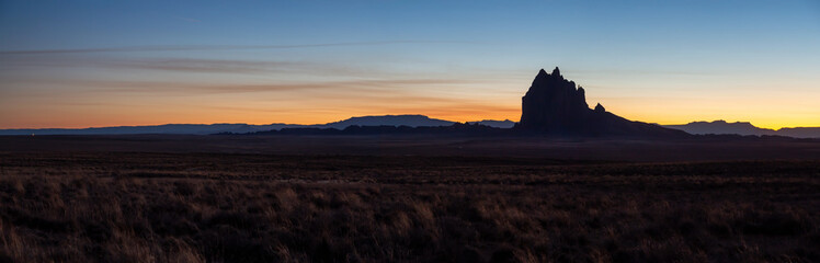 Dramatic panoramic landscape view of a dry desert with a mountain peak in the background during a vibrant sunset. Taken at Shiprock, New Mexico, United States.