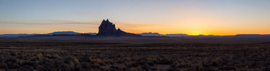 Striking panoramic landscape view of a dry desert with a mountain peak in the background during a vibrant sunset. Taken at Shiprock, New Mexico, United States.