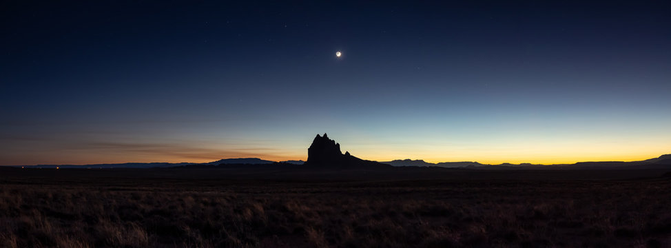 Dramatic panoramic landscape view of a dry desert with a mountain peak in the background during a clear night sky after sunset. Taken at Shiprock, New Mexico, United States.