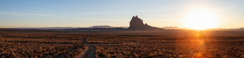 Striking panoramic landscape view of a dirt road in the dry desert with a mountain peak in the background during a vibrant sunset. Taken at Shiprock, New Mexico, United States.