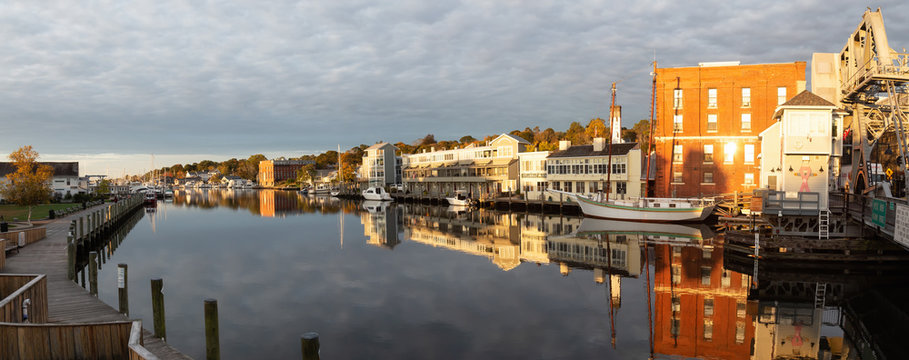 Mystic, Stonington, Connecticut, United States - October 26, 2018: Panoramic view of old historic homes by the Mystic River during a vibrant sunrise.