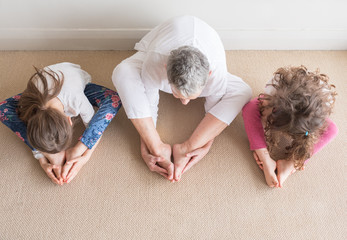 Directly above view of older woman sitting with young children in yoga stretch posture - grandmother teaching grandchildren yoga concept (selective focus)