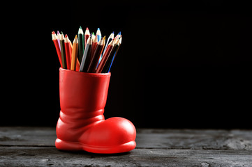 colored pencils in a red boot on