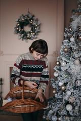 Woman decorating Christmas tree holding  basket