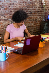 Happy black woman working at table in coworking office