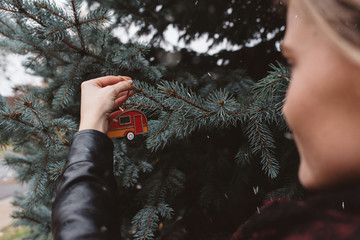 A women in her twenties decorating a tree in the snow at christmas time