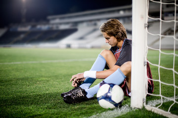 Young football player tying shoelaces in football stadium