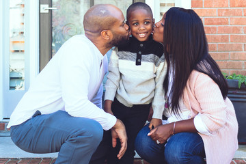 Parents kissing their young son