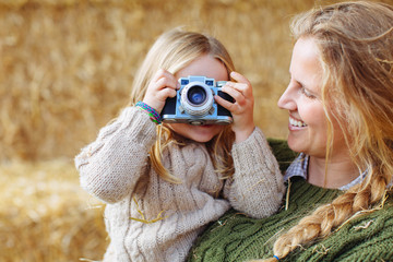 Mother and her daughter taking a photo with old camera.
