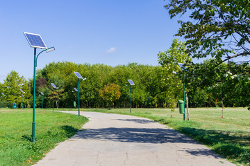 Park alley illuminated by solar powered street lights in Tineretului Park, Bucharest, Romania