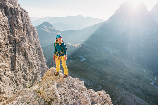 Female alpinist standing on high mountain peak in the sunset